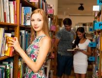 Belle étudiante de jeune femme dans la bibliothèque Photographie stock libre de droits