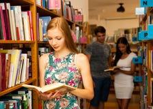 Belle étudiante de jeune femme dans la bibliothèque Photographie stock