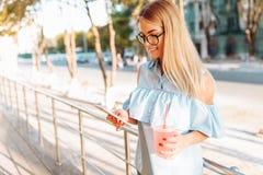 Belle étudiante en verres avec le cocktail à disposition se tenant photographie stock libre de droits