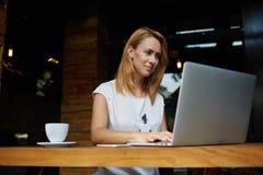 Belle étudiante européenne s'asseyant avec l'ordinateur portable portatif dans l'intérieur moderne de café, Photographie stock