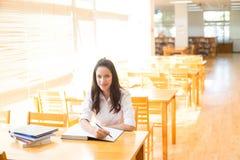 Belle étudiante indienne lisant un livre dans la bibliothèque avec le Se Photo stock