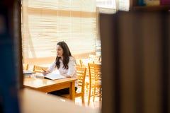 Belle étudiante indienne lisant un livre dans la bibliothèque avec le Se Images stock