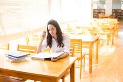 Belle étudiante indienne lisant un livre dans la bibliothèque avec le Se Photographie stock