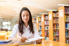 Belle étudiante indienne lisant un livre dans la bibliothèque avec le Se Images libres de droits