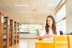 Belle étudiante indienne lisant un livre dans la bibliothèque avec le Se Image stock