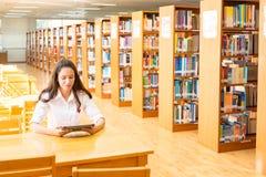 Belle étudiante indienne lisant un livre dans la bibliothèque avec le Se Photographie stock libre de droits