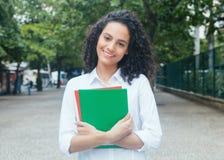 Belle étudiante latine avec les cheveux bouclés et la chemise blanche images libres de droits