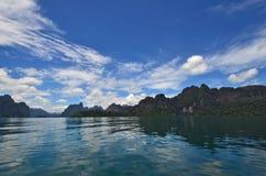 Belle acqua e montagne sotto cielo blu Fotografie Stock