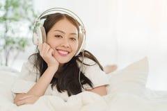 Belle adolescente à l'aide du smartphone avec l'écouteur à la maison Photographie stock