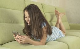 Belle adolescente ayant l'amusement communiquant sur le smartphone Photo stock