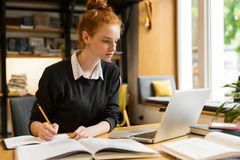 Belle adolescente d'une chevelure rouge à l'aide de l'ordinateur portable image stock