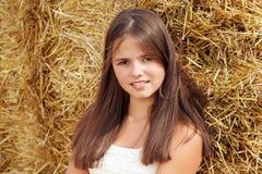 Belle adolescente de sourire s'asseyant près d'une balle de foin Photo stock