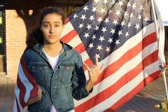 Belle adolescente ethnique devant un drapeau d'U S Image stock