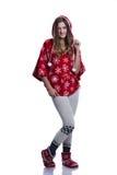 Belle adolescente gaie posant dans le studio Hoodie rouge de port d'hiver avec des flocons de neige D'isolement sur le fond blanc Image stock