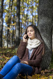 Belle adolescente s'asseyant et parlant du téléphone Photo stock