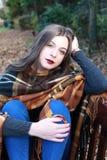 Belle adolescente s'asseyant sur un banc de parc en automne Photographie stock libre de droits