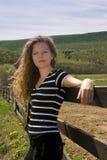 Belle adolescente se penchant sur une frontière de sécurité Photographie stock libre de droits