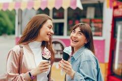 Belle amiche che camminano nel parco e nel gelato andante fotografie stock