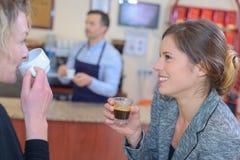 Belle amiche che parlano e che bevono caffè fotografia stock libera da diritti