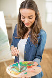 Belle artiste de jeune femme avec le sourire de pinceau et de palette Photographie stock libre de droits