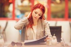 Belle, attirante jeune femme avec les cheveux rouges détendant en ville, café de rue photographie stock libre de droits