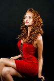 Belle, audacieuse fille red-haired dans une robe rouge Photographie stock