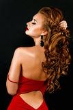 Belle, audacieuse fille red-haired dans une robe rouge Photos stock