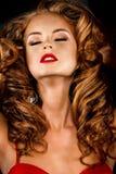 Belle, audacieuse fille red-haired dans une robe rouge Image libre de droits