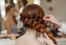 Belle, avec longtemps, la fille velue rousse, coiffeuse tisse une tresse française, plan rapproché dans un salon de beauté photos libres de droits