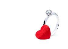 Belle bague à diamant et un coeur rouge de feutre sur le fond blanc Photo libre de droits