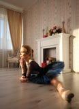 Belle ballerine de jeune femme étirant le réchauffage dans l'intérieur à la maison, fente sur le plancher, vue de côté Image stock