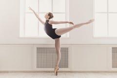 Belle ballerine en position de ballet d'arabesque photographie stock
