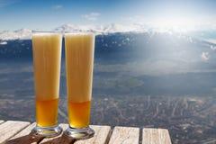 Belle bière froide savoureuse sur une table en bois sur le backgrou de montagne Photos stock
