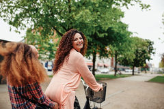 Belle bicyclette d'équitation de femme avec son ami Images stock