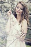 Belle blonde avec la belle coiffure dans la robe bleue de vintage dans une magnolia luxuriante de jardin de ressort Images stock