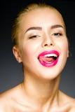 Belle blonde avec les lèvres roses colorées collant sa langue Image libre de droits
