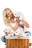 Belle blonde avec un petit chiot blanc de Labrador Photographie stock libre de droits