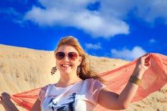 Belle blonde avec un tissu rose dans le désert Photos stock