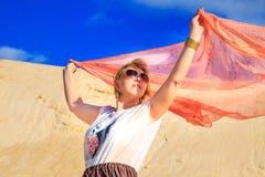 Belle blonde avec un tissu rose dans le désert Photographie stock libre de droits