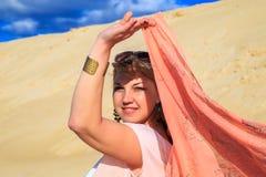 Belle blonde avec un tissu rose dans le désert Image stock