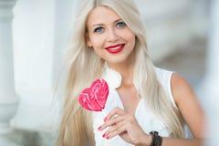 Belle blonde avec une lucette en forme de coeur Photographie stock libre de droits