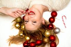 Belle blonde avec une sucrerie de Noël se trouvant sur un backgro blanc Image libre de droits