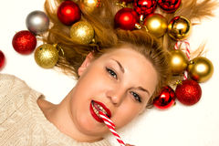 Belle blonde avec une sucrerie de Noël se trouvant sur un backgro blanc Photos stock