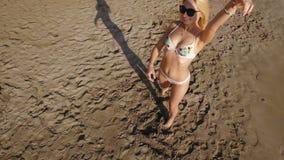 Belle blonde dans des lunettes de soleil posant pour l'appareil-photo sur la plage banque de vidéos