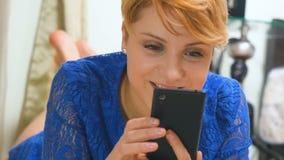 Belle blonde dans la transmission de messages bleue de robe sur le smartphone clips vidéos
