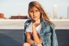 Belle blonde dans la veste de denim avec la planche à roulettes photo libre de droits