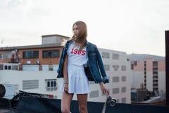 Belle blonde dans la veste de denim avec la planche à roulettes photographie stock libre de droits