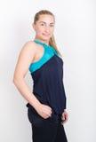 Belle blonde dans une chemise de sports, des shorts noirs et des espadrilles colorées, posant Photos stock