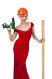 Belle blonde dans une robe rouge avec un foret électrique Images stock