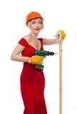 Belle blonde dans une robe rouge avec un foret électrique Photographie stock libre de droits
